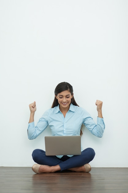 Cheerful Young Woman Working On Laptop On Floor Photo