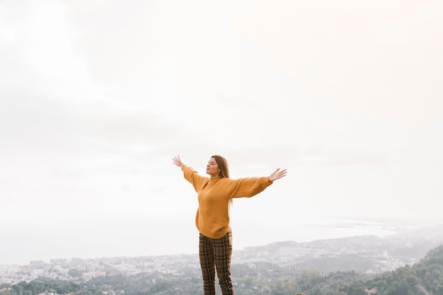 Cheering woman enjoy the beautiful view at mountain peak against sky Free Photo