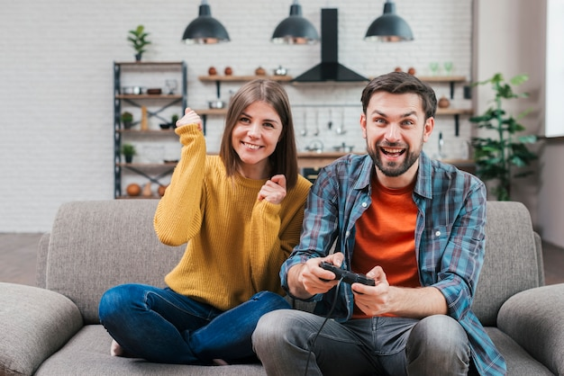 Cheering young couple sitting on sofa playing the video game Free Photo