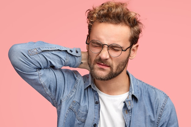 Cheerless man gets stiff neck, suffers from pain as has sedentary lifestyle and works for long time at computer, frowns face in dissatisfaction, wears spectacles and denim shirt, stands indoor Free Photo