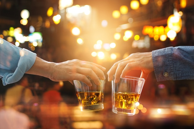 Cheers clinking of friends with bourbon whisky drink in party night after work on colorful Premium Photo