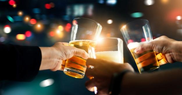 Приветствия, звенящие друзьями с пивным напитком в вечеринке ночью после работы Premium Фотографии