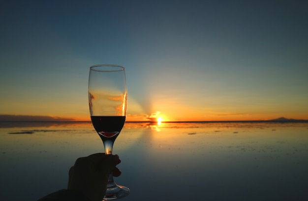 Cheers to the gorgeous sunset on the mirror effect of uyuni salt flats, bolivia, south america Premium Photo