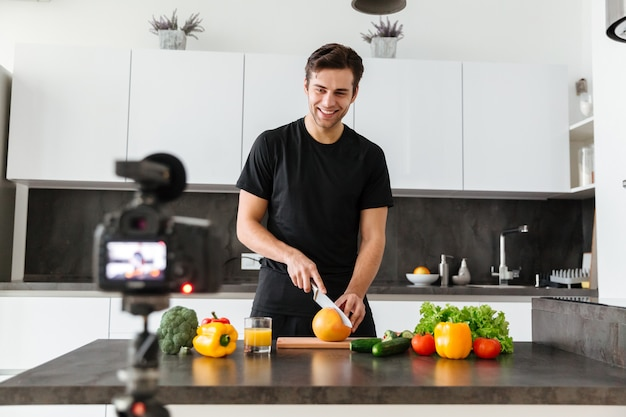 Cheery young man filming his video blog episode Free Photo