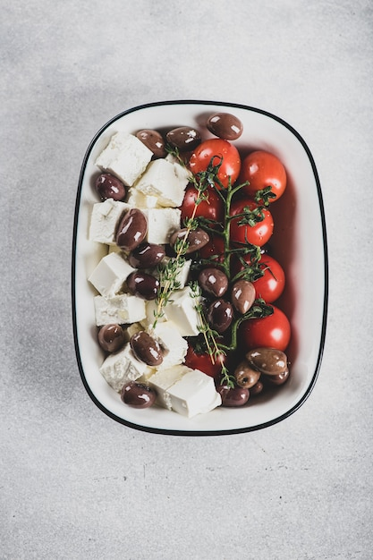 Chees feta, olive oil, kalamata olives and cherry tomatoes for baking , view from above Premium Photo
