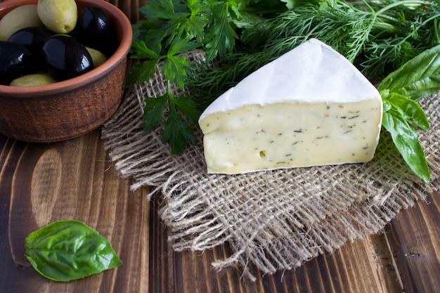 Сыр и оливки на деревянных фоне Premium Фотографии