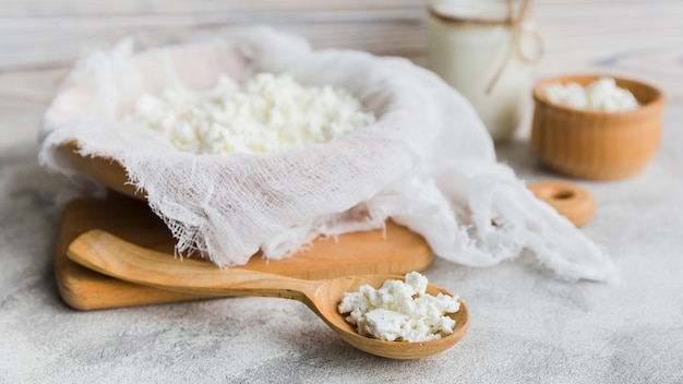 Ricotta cheese in a wooden bowl with a wooden spoon of it in front