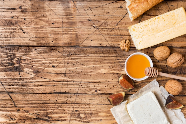 Cheese, baguette honey and nuts snacks on the rustic wooden table top with copy space. Premium Photo