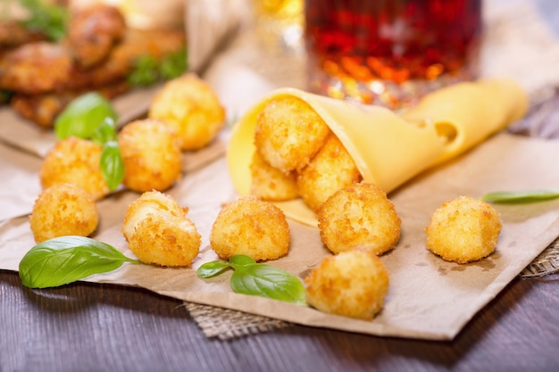 Сырные шарики с листьями базилика на деревянном столе Premium Фотографии