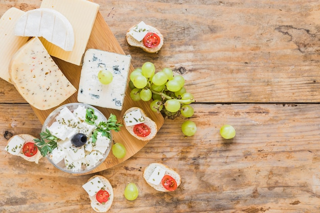 Cheese blocks and grapes with bread on wooden table Free Photo