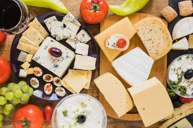 Cheese blocks and slices with tomatoes, grapes and green chili pepper on table Free Photo
