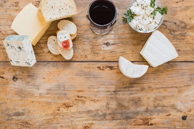 Cheese blocks with red wine and bread on wooden desk Free Photo