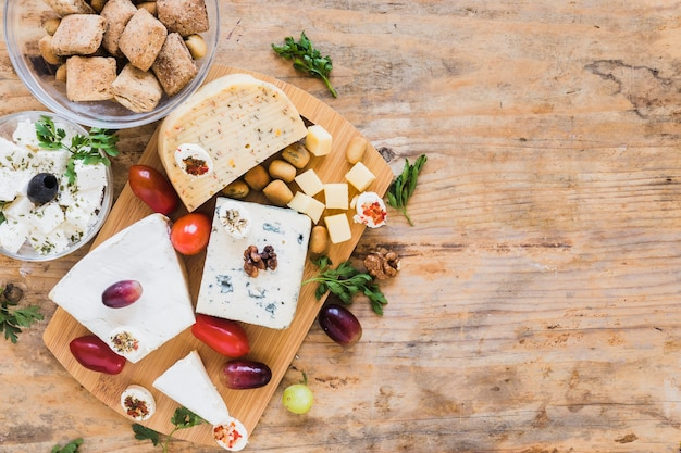 Cheese blocks with tomatoes, parsley and grapes on wooden table Free Photo
