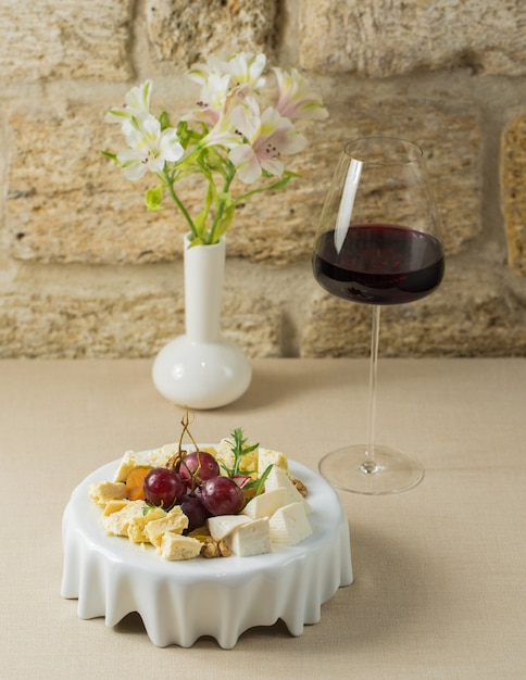 Cheese board witt a glass of french red wine Free Photo