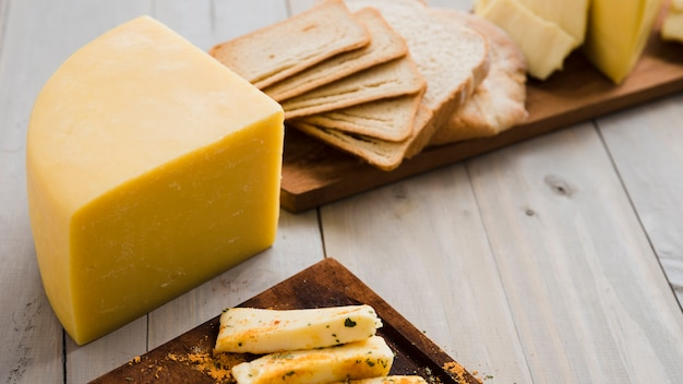 Cheese chunk and bread slices on wooden board over the table Free Photo