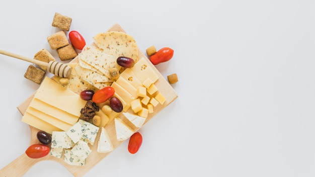 Cheese cubes and slices with cheery tomatoes, walnuts, grapes and cookies on white backdrop Free Photo
