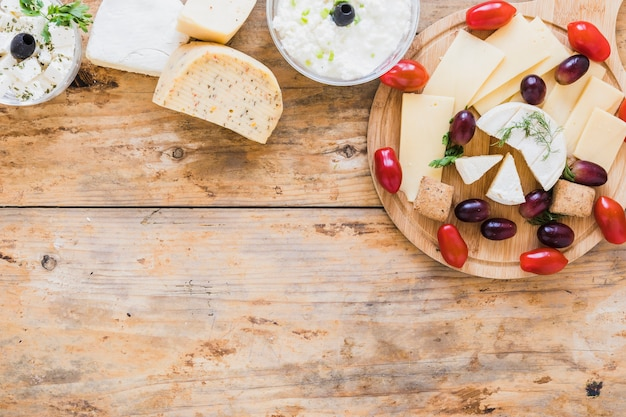 Cheese dip and blocks with grapes and tomatoes on wooden desk Free Photo
