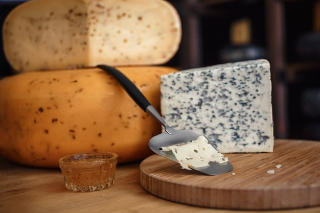 Cheese heads with slices and knives on a wooden board with an interior Premium Photo