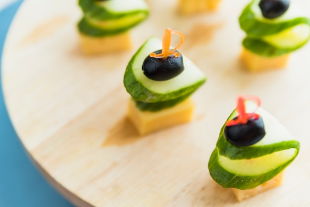 Cheese, olive and cucumber on plastic skewer on chopping board Free Photo