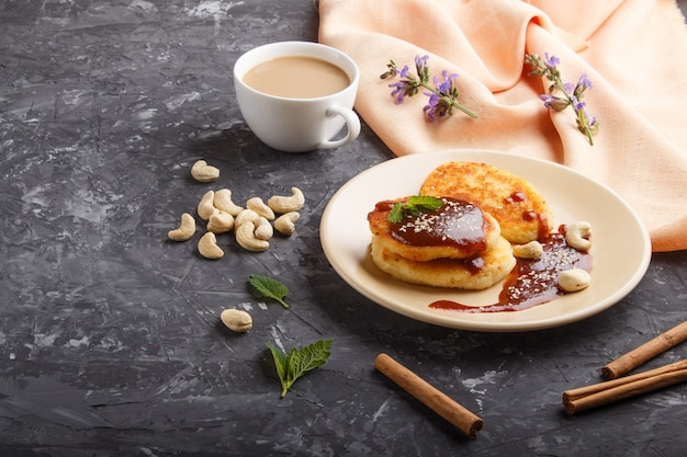 Cheese pancakes with caramel sauce on a beige ceramic plate and a cup of coffee on black concrete Premium Photo