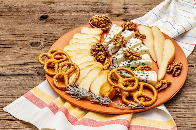 Cheese plate antipasti with smoked and blue cheese, crackers, honey, walnuts and ripe pear Premium Photo