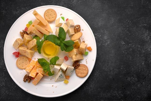 Сырная тарелка, сырное ассорти с мятой, цукатами, медом и печеньем, на белой тарелке, на темном фоне Premium Фотографии