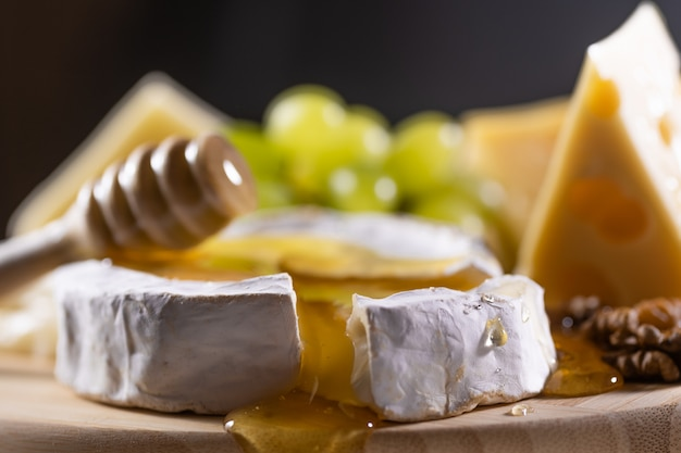 Cheese plate, honey pouring on camembert cheese Premium Photo