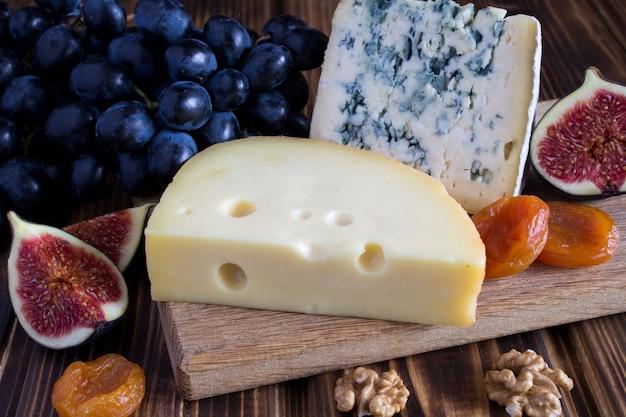 茶色の木製の背景にチーズプレート Premium写真