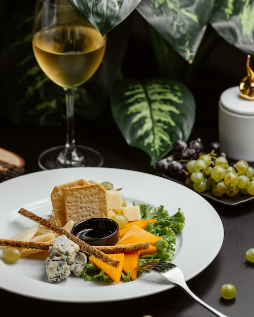 Cheese plate with bread sticks and crackers Free Photo