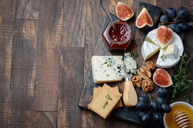Сырная тарелка с фруктами и орехами. Premium Фотографии