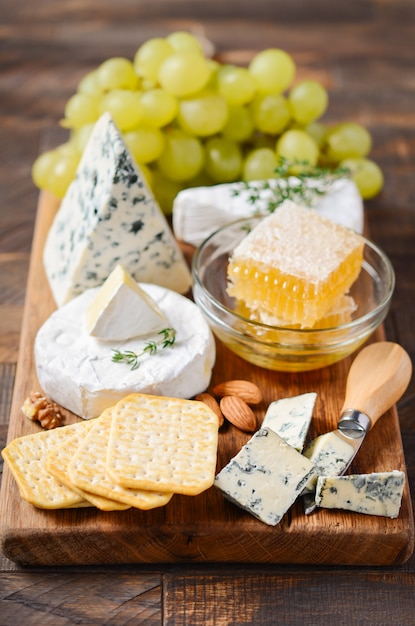 Cheese plate with grapes, crackers, honey and nuts on a wooden table Premium Photo