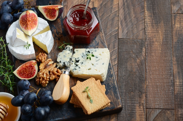 Cheese plate with grapes, figs, crackers, honey, plum jelly, thyme and nuts. Premium Photo