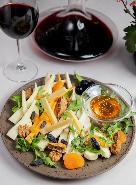 Cheese plate with nuts raisins arugula olives and glass of wine Free Photo