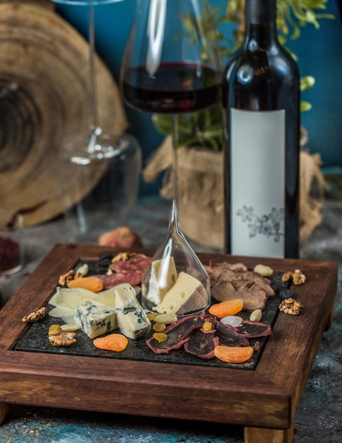 Cheese platter and a glass with a bottle of red wine Free Photo