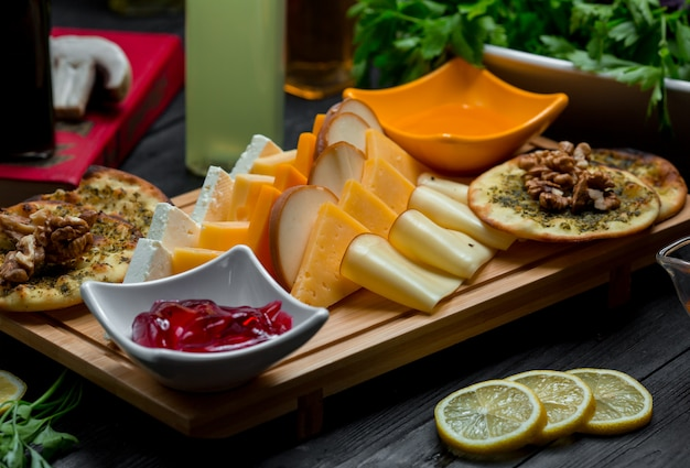 Cheese platter with cheese variations, crackers, nuts and strawberry jam Free Photo