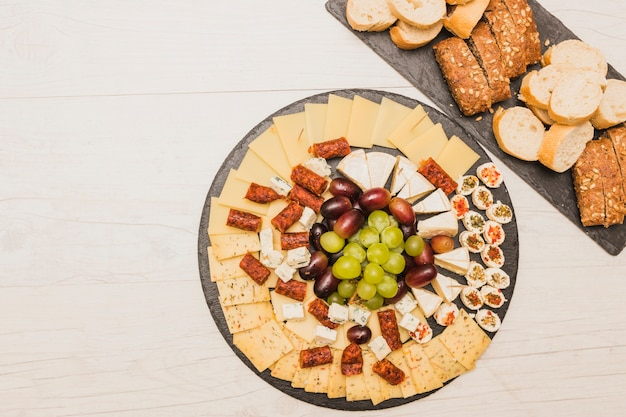 Cheese platter with grapes; smoked sausages and bread Free Photo