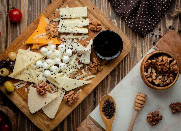 Cheese platter with olives and walnuts. Free Photo