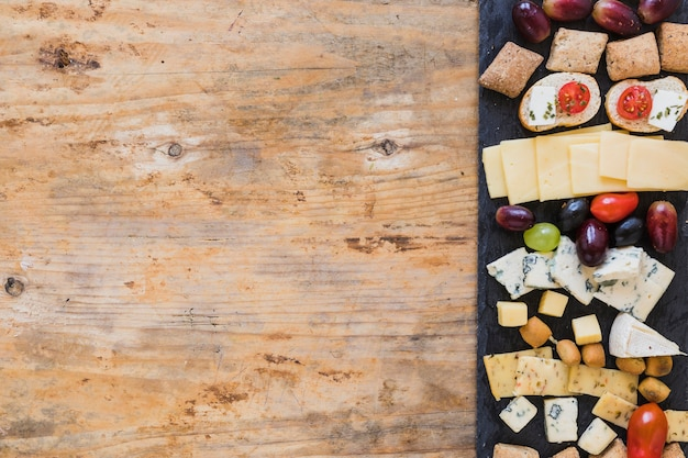 Cheese platters on black slate board over the table Free Photo