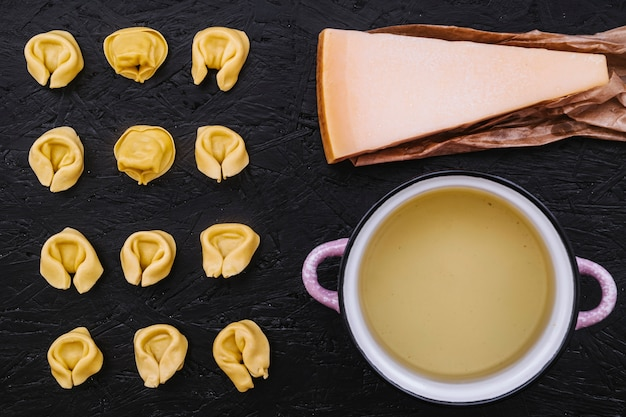 Cheese and saucepan near stuffed pasta Free Photo