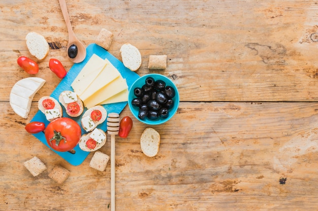 Cheese slices, tomatoes, bread, and olives on wooden table Free Photo