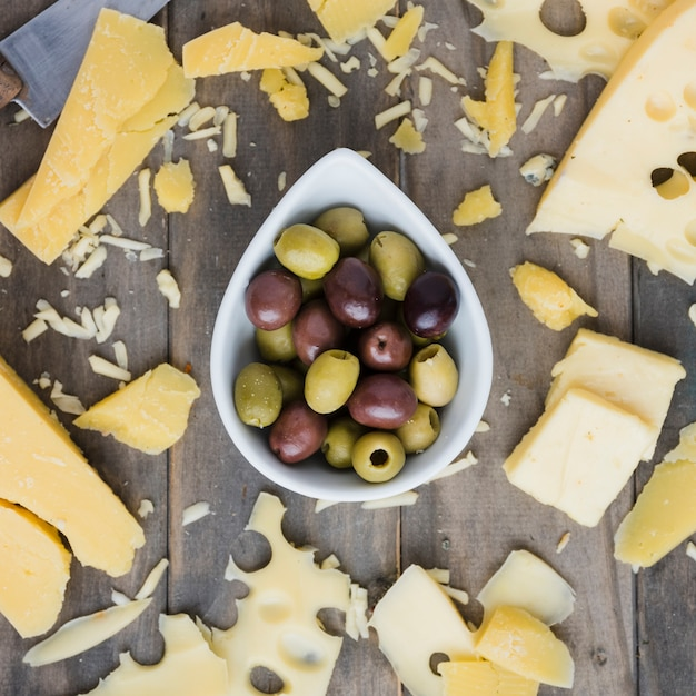 Cheese spread near the olive bowl on wooden table Free Photo