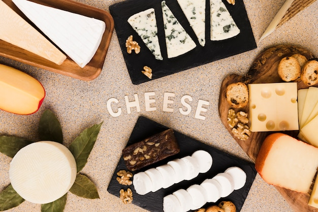 Cheese text surrounded with variety of cheeses slices; walnut and bay leaves over textured surface Free Photo