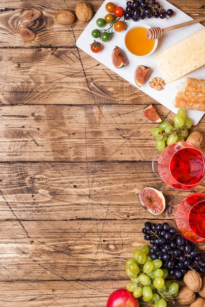 Cheese, wine, baguette grapes figs honey and snacks on the rustic wooden table top with copy space. Premium Photo
