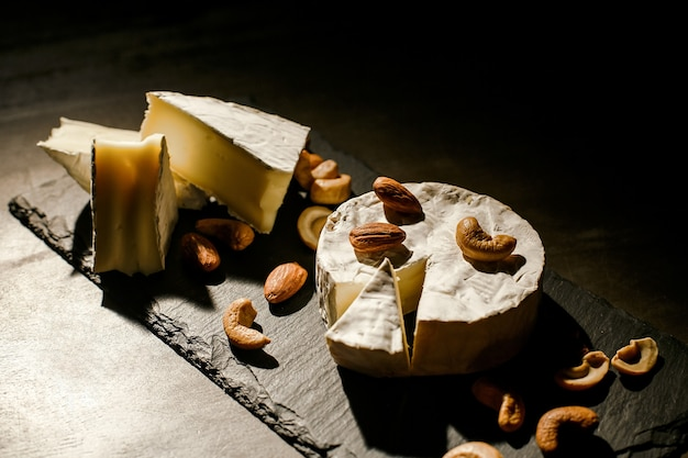 Cheese with nuts on dark background Premium Photo