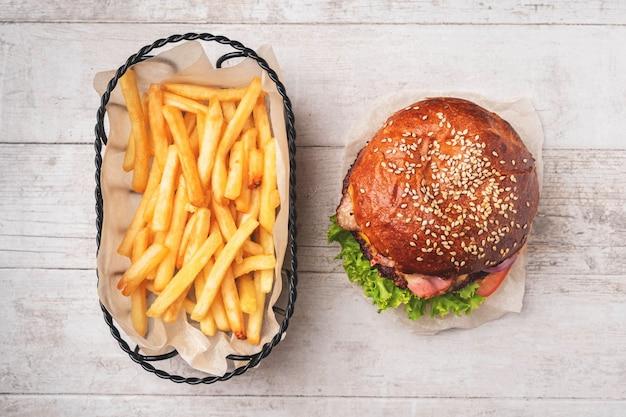 Cheeseburger and fries in a metal basket. Premium Photo