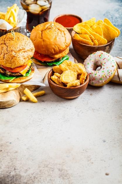 Cheeseburgers, french fries, nachos, donuts, soda and nuggets Premium Photo