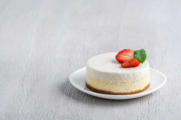 明るい木製の背景に新鮮なイチゴとチーズケーキケーキ。 Premium写真