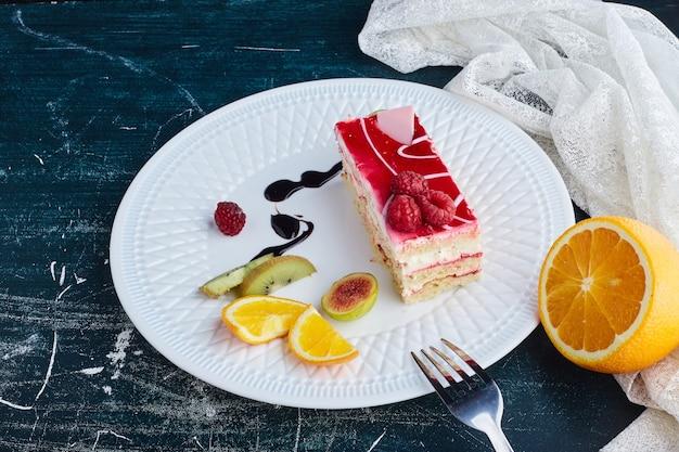 Fetta di torta di formaggio con sciroppo di lamponi in un piatto bianco. Foto Gratuite