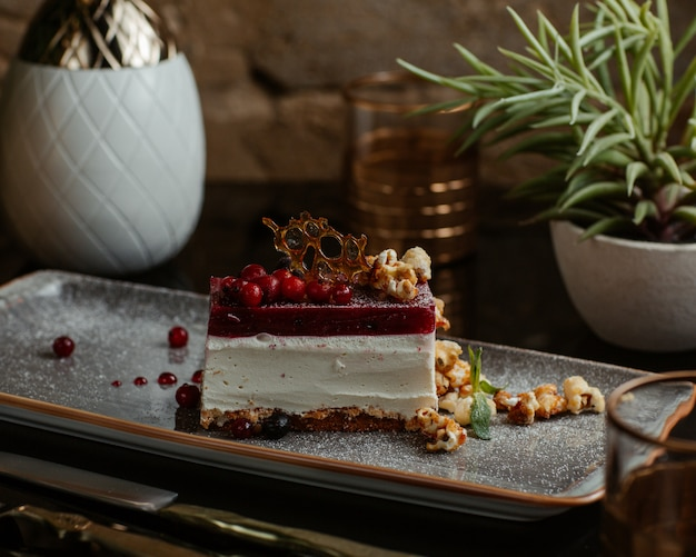 Cheesecake slice with red berry sauce and crockery. Free Photo