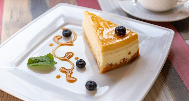 Cheesecake with blueberry sauce on white plate and cup of coffee on wooden table Premium Photo